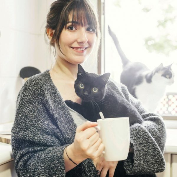 happy-woman-with-cup-coffee-holding-her-cat_23-2147860403